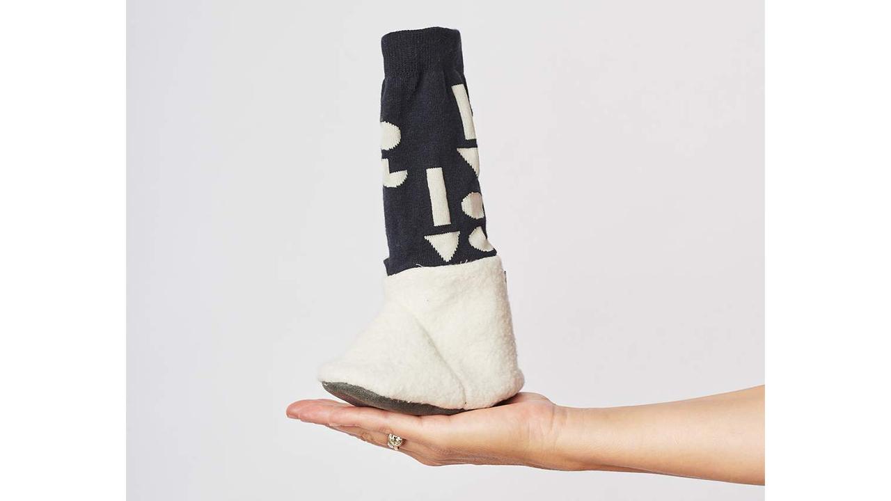 Foto de una mano sosteniendo una bota de bebé con un diseño en blanco y negro