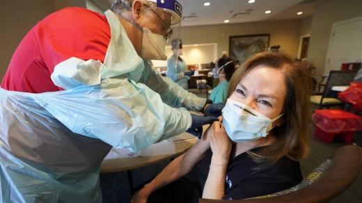 La trabajadora de salud Pam Peter, derecha, se prepara para recibir su segunda ronda de la vacuna COVID-19 en Florida.