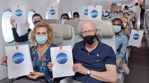 Los pasajeros exhiben sus certificados conmemorativos a bordo del vuelo de Emirates.