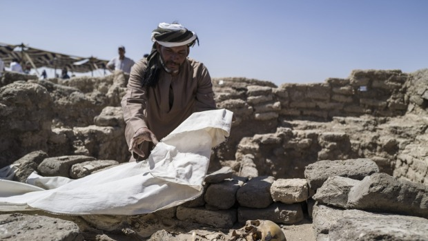 Un trabajador cubre los restos óseos encontrados en el sitio de una ciudad perdida de 3.000 años de antigüedad en Luxor, Egipto.